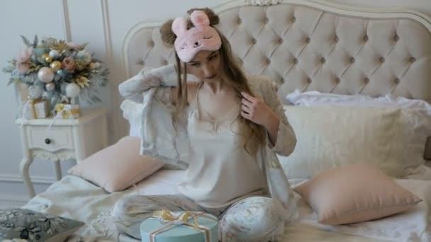 Boldog fiatal gyönyörű lány pizsama kicsomagolja karácsonyi ajándék az ágyon. Szilveszteri hangulatban