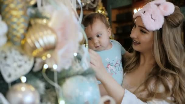 Mother and daughter decorate and admire a Christmas tree