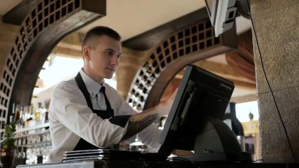 Muž, nebo číšník v odbavovací přepážce s pokladní v restauraci