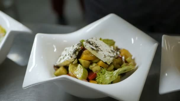 Chef puts Greek salad on a dish in the restaurant