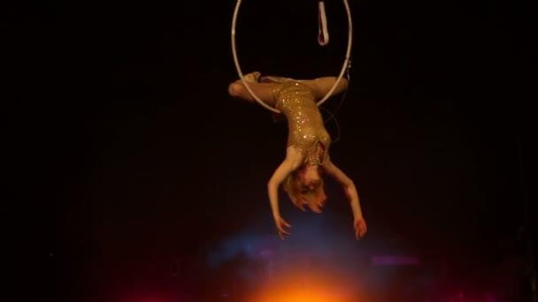 Junges Mädchen führt die akrobatischen Elemente im Luftring auf