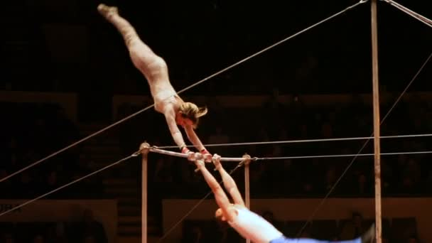 Acrobats perform exercises on the bar in the circus arena