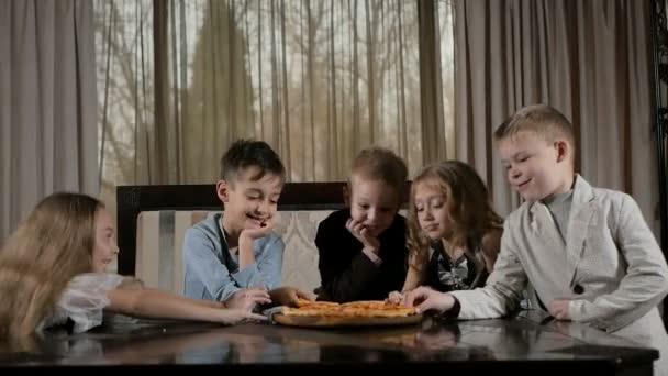 Happy kids eat pizza in the restaurant