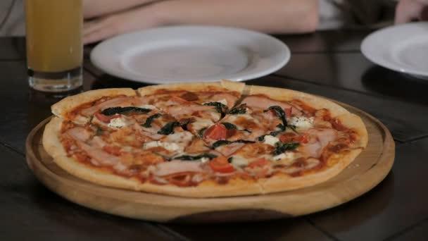 Dětské ruce s pizza plátky z dřevěného stolu