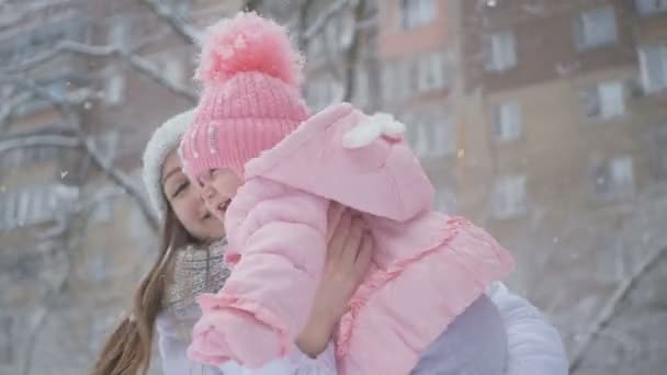 Young mother and daughter happy together in the snowfall at park