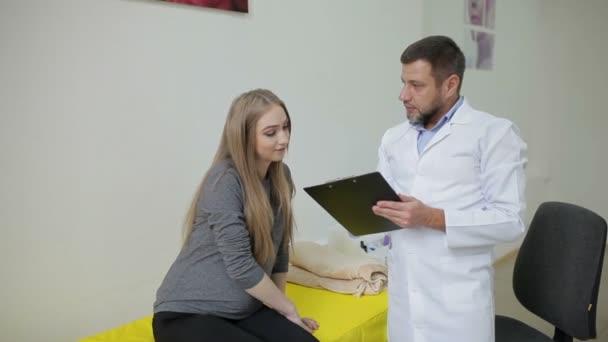 Arzt untersucht Schwangere und schreibt Ergebnisse in die Gesundheitskarte