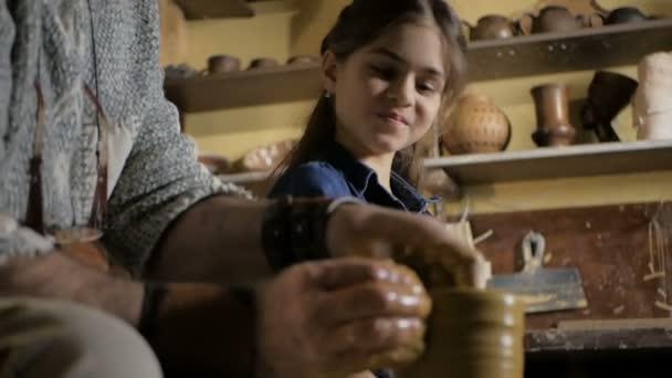Töpferei. Opa lehrt Enkelin Töpfern