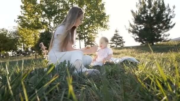 Zeitlupe der Mutter füttert Tochter bei Sonnenuntergang mit Gemüse