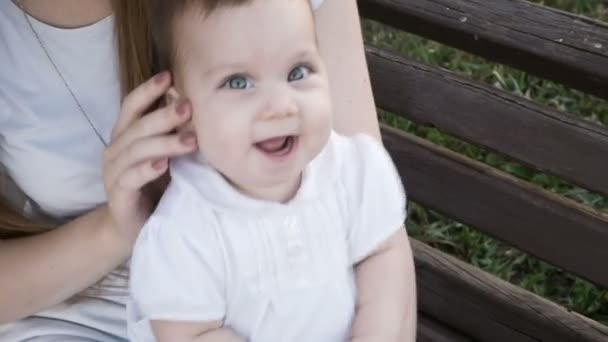 glückliches kleines Mädchen sitzt auf der Bank im Park