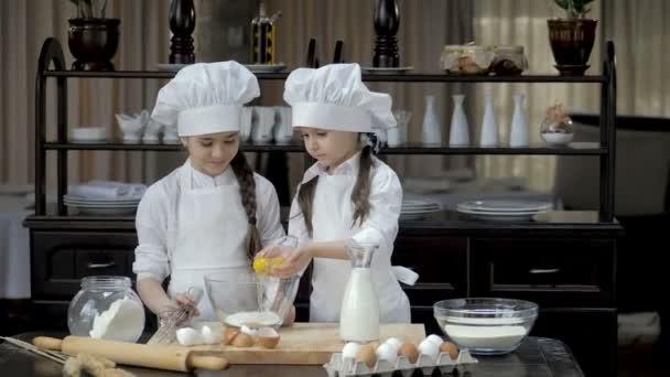 Vtipné mladé dívky připravují těsto v kuchyni