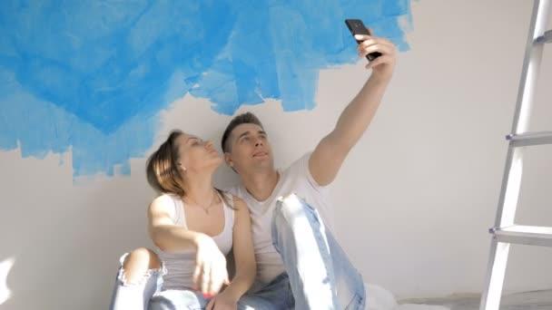 Šťastný pár sedí na podlaze u žebříku a při opravě
