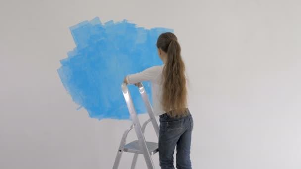 junges Mädchen bemalt Tapete mit Walze im Raum mit blauer Farbe