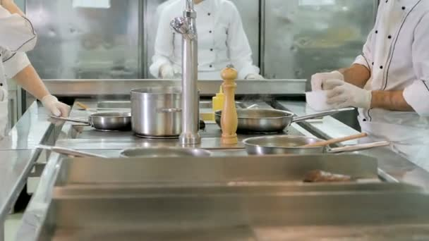 Kuchaři připravují jídlo na sporáku v kuchyni restaurace nebo hotelu