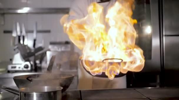Kuchaři a kuchařka vaří na zelenině v wok na restaurační kuchyni