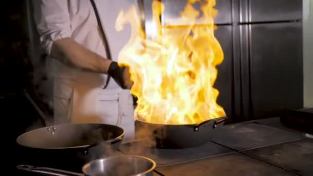 Chefs cooks and doing flambe on vegetables in wok on restaurant kitchen