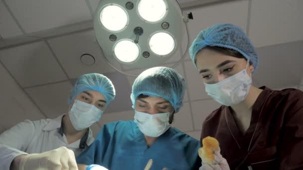 Surgeons are operating. Resuscitation medicine team wearing masks holding medical tools