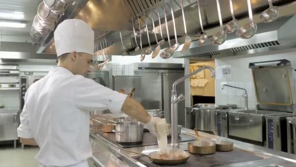 Szakácsok szakácsok és ezzel flambírozott a zöldségek serpenyőben étterem konyha