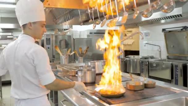 Kuchaři vaří a dělají flambe na zelenině v pánvi v kuchyni restaurace