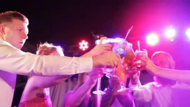 Junge freundliche Leute stoßen mit Cocktails im Open-Air-Nachtclub an
