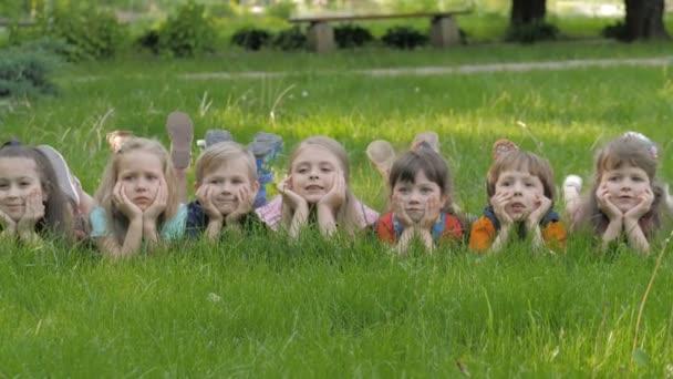 Gruppe fröhlicher Kinder liegt auf grünem Gras im Frühlingspark