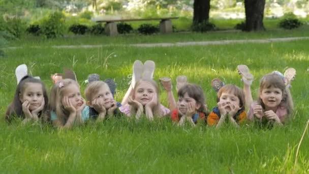 Boldog gyermekek, szabadban, tavaszi park zöld füvön feküdt csoportja