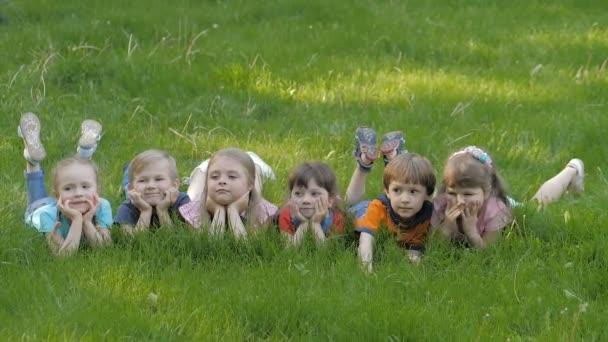 Skupina šťastných dětí leží na zelené trávě venku v parku na jaře