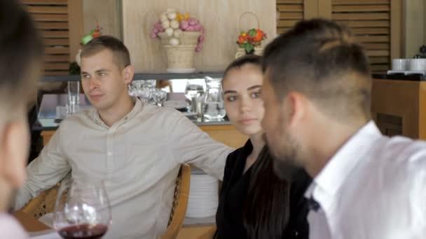 Mladí přátelé se v restauraci baví pít červené víno. Koncepce přátelství mládeže