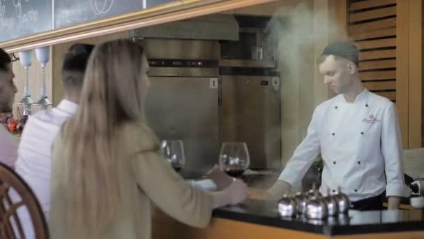 Kuchaři vaří v bílé uniformě pro klienty na baru v otevřené kuchyni restaurace