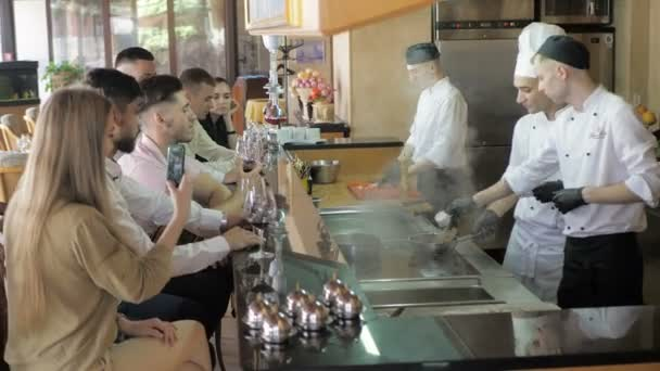 Chefs cook in white uniform for clients on the bar table at the open kitchen of the restaurant