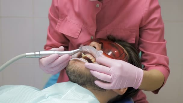 Female dentist with male patient doing the cleaning of the tooth in dentistry