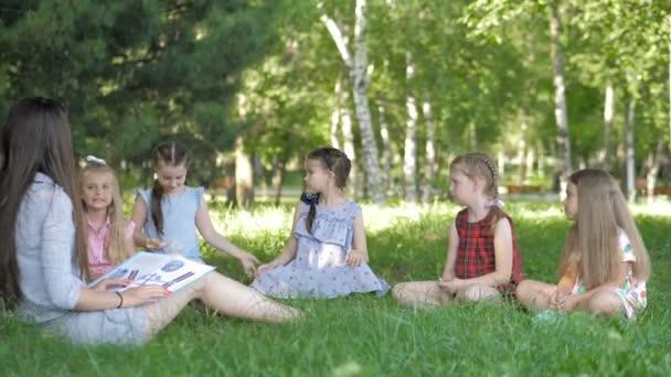Děti a vzdělávání, mladá žena v práci jako pedagožka čtení knihy pro chlapce a dívky v parku