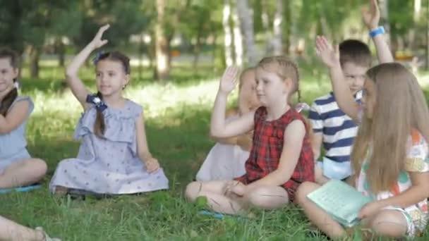 Gyermekek és oktatás, fiatal nő a munkahelyen, mint pedagógus könyvet olvasni a fiúk és lányok a parkban
