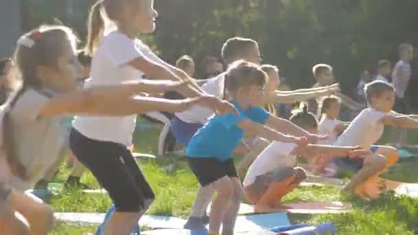 große Gruppe von Erwachsenen und Kindern bei einem Yoga-Kurs im Park