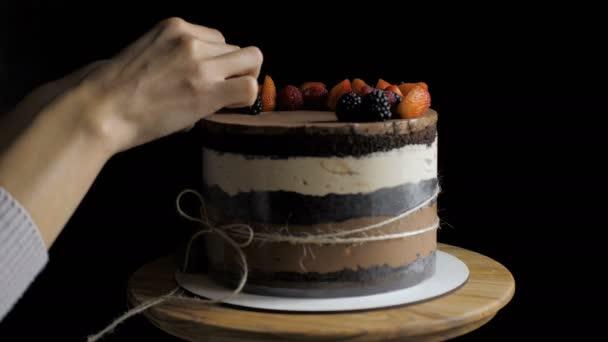 Ruce cukrářské šéfkuchaře zdobí vrchol nahého dortu