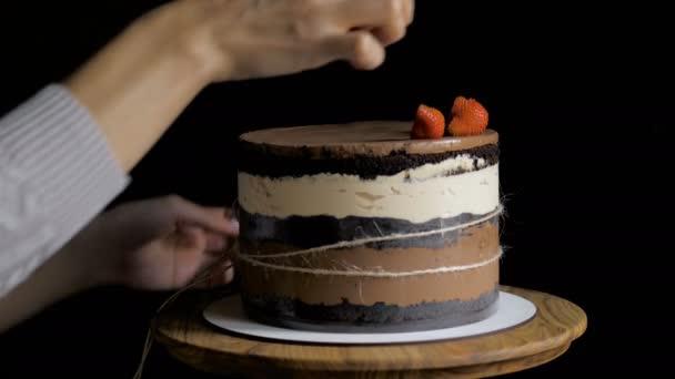 A keze a cukrász díszítik a tetején a meztelen torta
