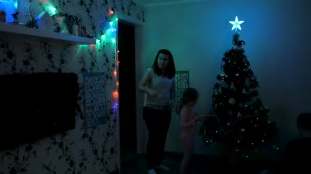 The family light the Christmas tree in the dark