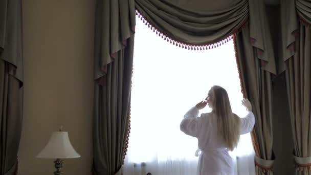 Frau im Bademantel bleiben in der Nähe des Fensters im Hotelzimmer