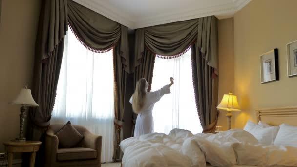 Woman in bathrobe stay near the window in hotel room