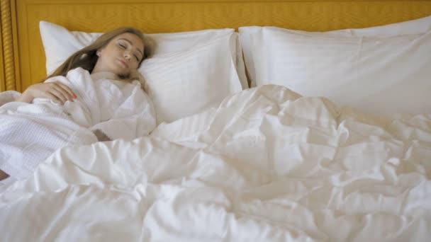 Krásná mladá dívka spící v hotelovém lože