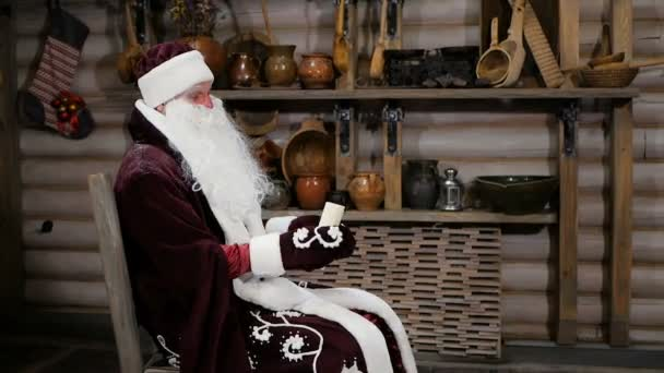 Ruský Santa Claus sedí v křesle a čte nové roky