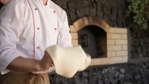 Šéfkuchař s pizzou v restauraci