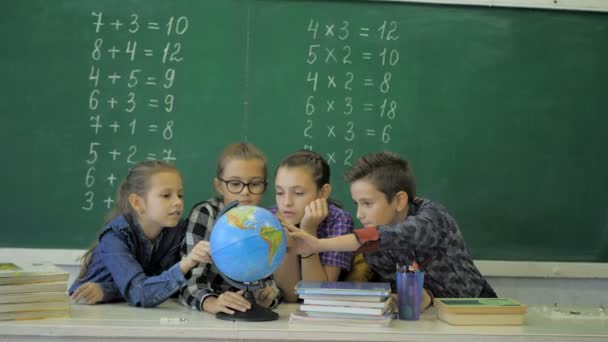 Geography lesson. Schoolmates are studying the globe on the background of a school board