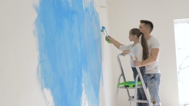 Vater und Tochter bemalen eine Wand in ihrem Haus mit einem Rollator