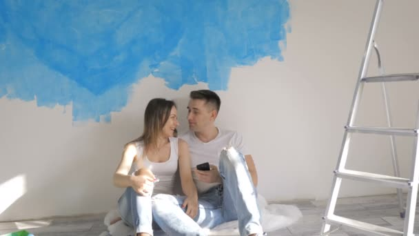 Couple talking about interior design on the background of painted wall