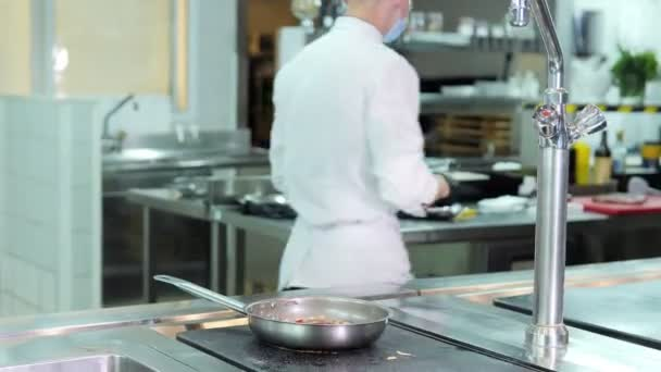 Chef in protective masks and gloves prepares food in the kitchen of a restaurant or hotel