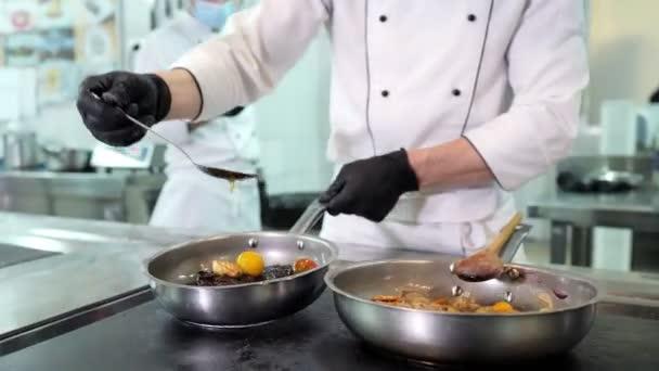A védőmaszkos szakácsok és kesztyűk ételt készítenek egy étterem vagy szálloda konyhájában.