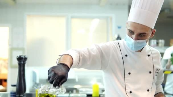 Köche in Schutzmasken und Handschuhen bereiten Essen in der Küche eines Restaurants oder Hotels zu