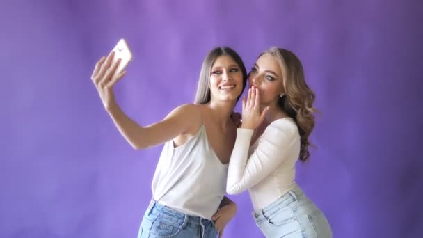 Two young and beautiful girls smiles in the Studio on an colourful background. Girls for advertising