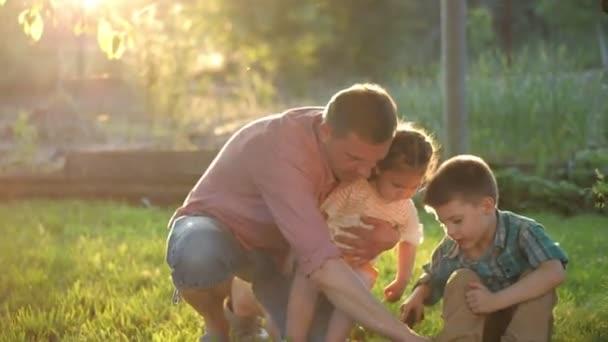 Zahradničení s dětmi. Šťastný mladý dědeček se svými vnoučaty pracující na zahradě