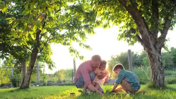 Gardening with a kids. Happy young grandfather with his grandchildren working in the garden